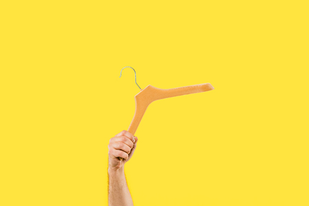 cropped shot of person holding wooden hanger isolated on yellow