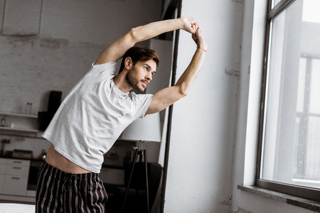 handsome young man in pajamas stretching and looking at window in the morning 版權商用圖片 - 112610858