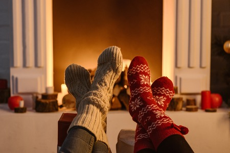 cropped view of women wearing winter socks with fireplace on background