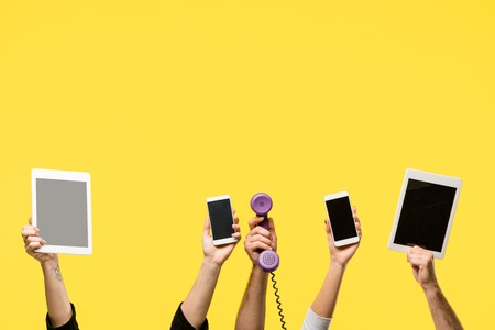 cropped shot of hands holding smartphones, digital tablets and handset isolated on yellow Banco de Imagens