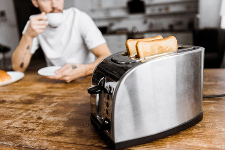 cropped shot of young man drinking coffee at home with toaster on foreground