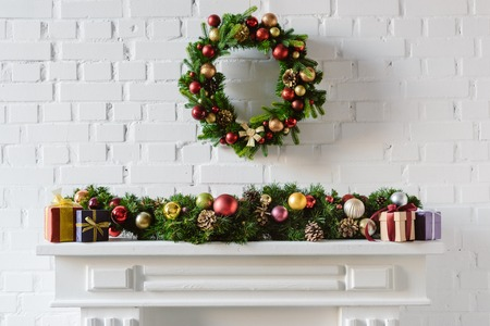 christmas wreath and decorations over fireplace mantel with white brick wall Stok Fotoğraf - 112611001