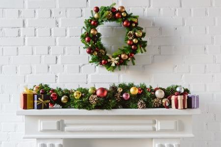 Corona de Navidad y adornos sobre la repisa de la chimenea con pared de ladrillo blanco.