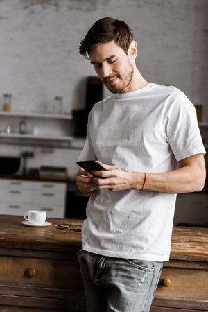 handsome young man using smartphone on kitchen at home Stok Fotoğraf