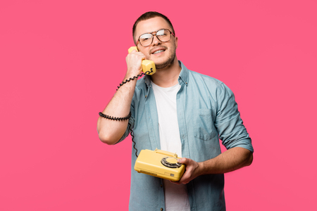 smiling young man in eyeglasses talking by vintage telephone and looking at camera isolated on pink