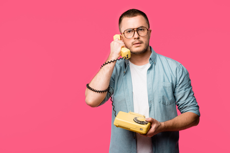 serious man in eyeglasses talking by vintage telephone and looking at camera isolated on pink
