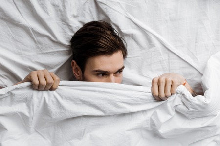top view of handsome young man hiding under blanket in bed at home and looking away 版權商用圖片 - 112611150