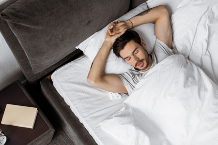top view of handsome bearded young man sleeping in bed