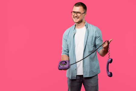 handsome young man in eyeglasses holding purple rotary phone and smiling at camera isolated on pink