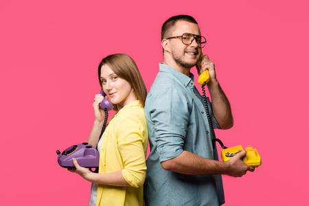 side view of happy young couple standing back to back and talking by rotary phones isolated on pink