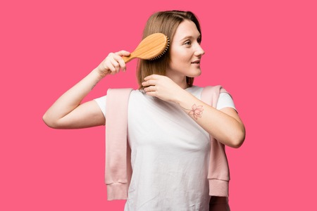 smiling young woman combing hair and looking away isolated on pink