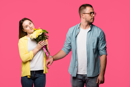 smiling young woman holding bouquet of flowers while standing in handcuffs with man looking away isolated on pink Stock Photo - 112619387