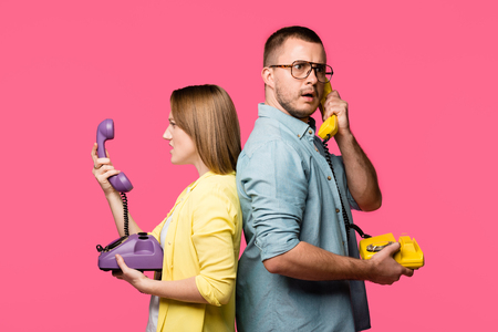 side view of angry young couple standing back to back and talking by rotary phones isolated on pink Stock Photo