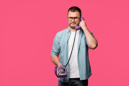 frowning young man talking by vintage telephone and looking at camera isolated on pink