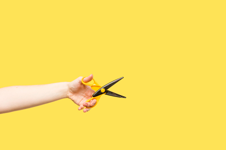 cropped shot of person holding scissors isolated on yellow