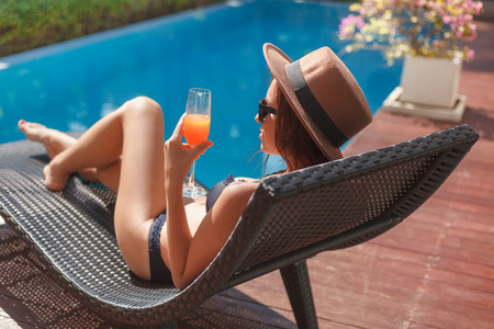 stylish young woman in bikini lying in sun lounge at poolside