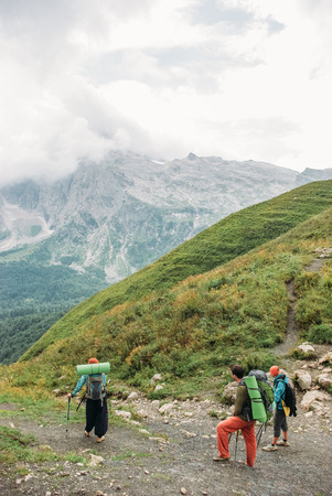 tourists with backpacks walking in mountains, Caucasus, Russia