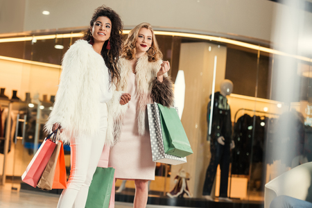 stylish young multiethnic women in fur coats holding paper bags while shopping together in mall Stockfoto