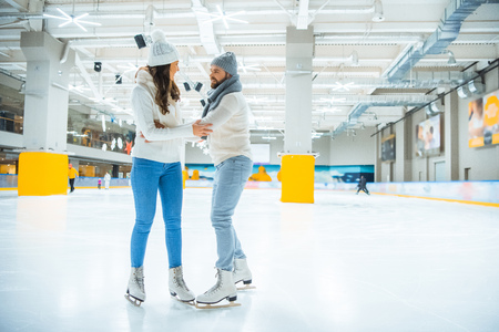 couple in knitted sweaters and hats skating together on ice rink