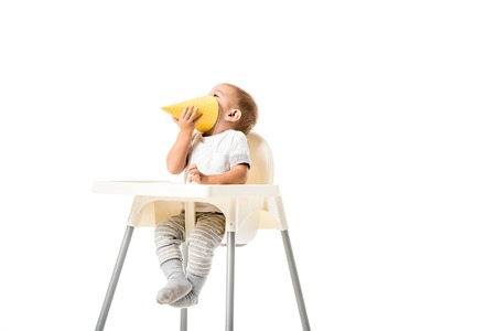 toddler boy holding yellow party hat and sitting in highchair isolated on white