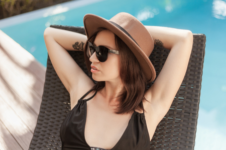 young woman in bikini and hat relaxing in sun lounge at poolside 写真素材