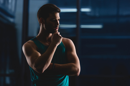 silhouette of thoughtful muscular sportsman in gym