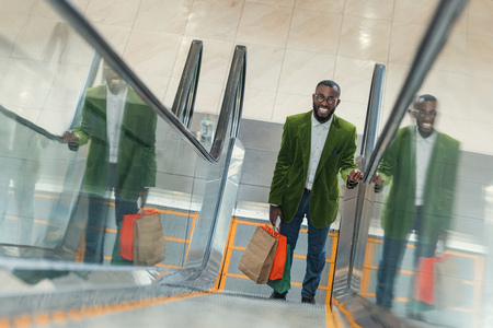 smiling fashionable man with shopping bag on escalator at mall
