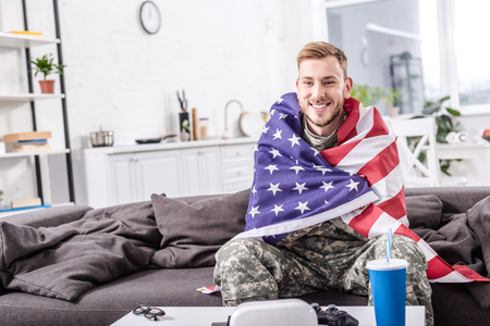 smiling army soldier covered in american flag sitting on couch and watching football match