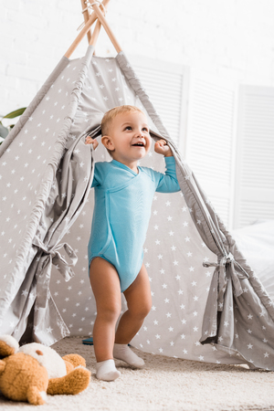 cute toddler boy in blue bodysuit smiling and standing in grey baby wigwam in nursery room