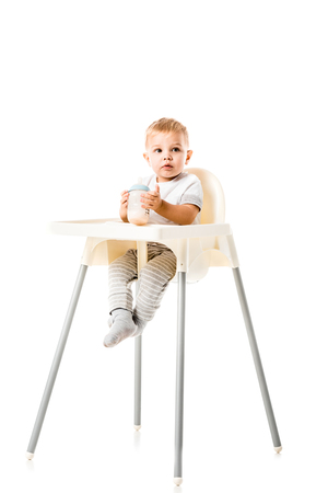adorable toddler boy holding baby bottle and sitting in highchair isolated on white Stock Photo - 112740208