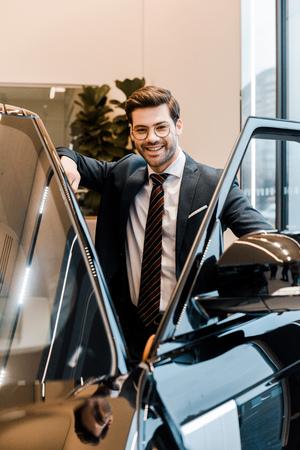 laughing businessman in eyeglasses posing near automobile in car salon 版權商用圖片