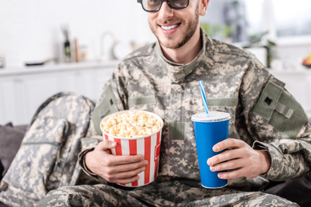 smiling soldier in 3d glasses watching movie with popcorn and soda water