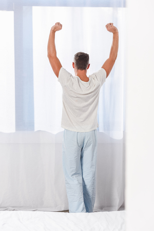 Back view of man stretching in room