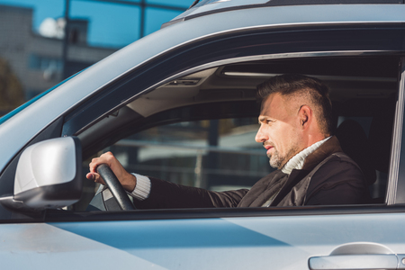 Handsome driver sitting in car and holding steer Stock Photo