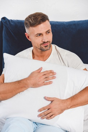 Handsome man holding pillow in room Stock fotó