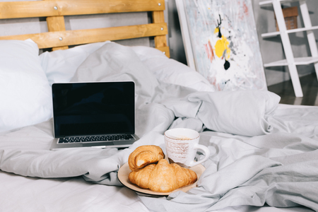 cup of coffee and croissants on plate and open laptop on bed Banque d'images - 112741846