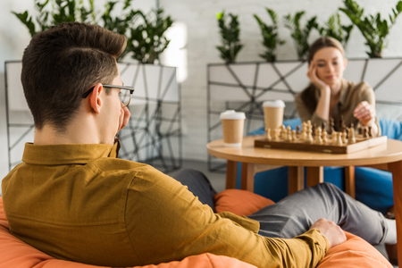 concentrated young man and woman playing chess