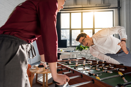 happy colleagues playing table football at modern office