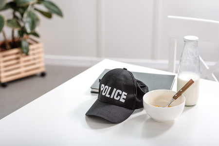notebook, police cap and bowl with breakfast on white table Banque d'images
