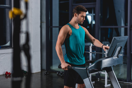 handsome sportsman training on treadmill in gym