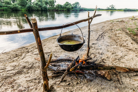 food preparing in cauldron on campfire at river shore, polesie, pripyat, Ukraine 스톡 콘텐츠