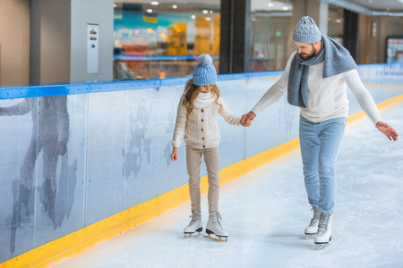 father and daughter in knitted sweaters skating on ice rink together Stockfoto - 112742973