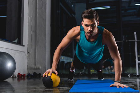 muscular sportsman doing push ups with medicine ball on yoga mat in sports center Stockfoto