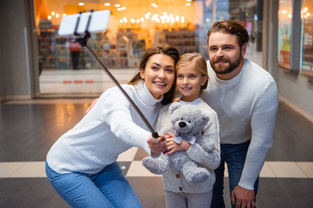 smiling family in white sweaters taking selfie on smartphone together