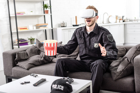 policeman with virtual reality headset on head holding popcorn bucket and sitting on couch