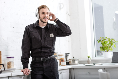 Handsome policeman listening to music with headphones in morning