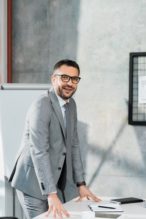 smiling handsome businessman in suit and glasses leaning on table and looking at camera in office Stock Photo