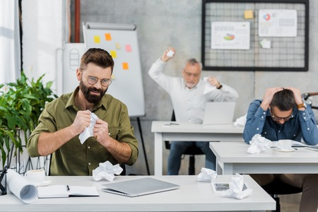 angry and sad businessmen tearing and throwing paper in office