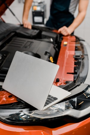 selective focus of laptop and auto mechanic at auto repair shop Stock Photo - 112746082