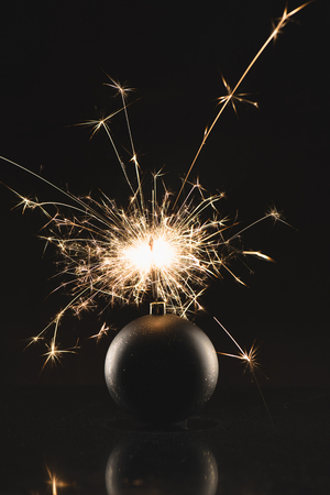 close up view of burning sparklers in christmas toy isolated on black Stock Photo